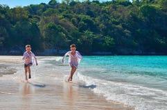 Παιδιά ψυχαγωγίας έννοιας στην παραλία Δύο γελώντας αγόρια τρέχουν στην τυρκουάζ παραλία θάλασσας στο υπόβαθρο την τροπική ζούγκλ Στοκ Εικόνα