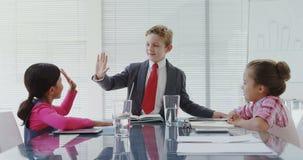 Παιδιά ως ανώτατα στελέχη επιχείρησης που διοργανώνουν μια συνεδρίαση στο δωμάτιο πινάκων 4K 4k φιλμ μικρού μήκους
