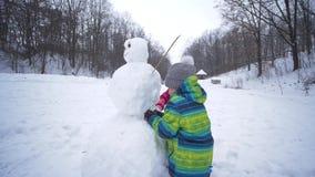 Παιδιά sculpts ένας χιονάνθρωπος στο χιόνι κατά τη διάρκεια των χιονοπτώσεων στις χειμερινές διακοπές απόθεμα βίντεο