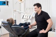 Παιδιατρικά χέρια τινάγματος οδοντιάτρων με το νέο ασθενή αγοριών στο οδοντικό γραφείο Στοκ Φωτογραφία