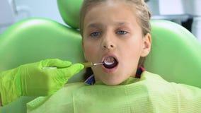Παιδιατρικός οδοντίατρος που ελέγχει τα δόντια με το στοματικό καθρέφτη, στερεότυπη οδοντική εξέταση απόθεμα βίντεο