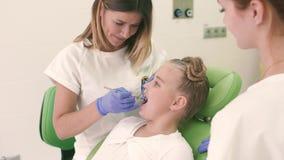 Παιδιατρικός οδοντίατρος που φαίνεται δόντια η οδοντική καρέκλα στο γραφείο Το κορίτσι κοιτάζει στον καθρέφτη και χαμογελά φιλμ μικρού μήκους