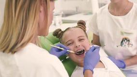 Παιδιατρικός οδοντίατρος που φαίνεται δόντια η οδοντική καρέκλα στο γραφείο Το κορίτσι κοιτάζει στον καθρέφτη και χαμογελά απόθεμα βίντεο