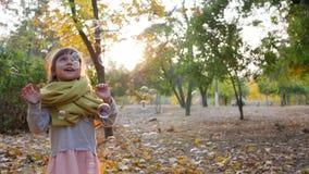 Παιδικά παιχνίδια με τις φυσαλίδες σαπουνιών στον ήλιο, ευτυχές μικρό κορίτσι που γελά στο φθινόπωρο απόθεμα βίντεο