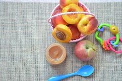 Παιδικές τροφές, φρούτα μωρών πολτοποίηση σε ένα βάζο γυαλιού, ροδάκινο, όμορφα ροδάκινα σε ένα καλάθι, παιχνίδι παιδιών ` s Appl Στοκ Εικόνες