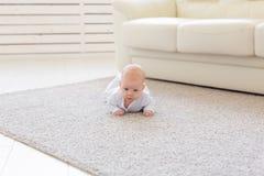 Παιδική ηλικία, babyhood και έννοια ανθρώπων - λίγο αγοράκι ή κορίτσι που σέρνεται στο πάτωμα στο σπίτι στοκ εικόνες