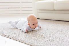 Παιδική ηλικία, babyhood και έννοια ανθρώπων - λίγο αγοράκι ή κορίτσι που σέρνεται στο πάτωμα στο σπίτι στοκ φωτογραφία με δικαίωμα ελεύθερης χρήσης