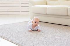 Παιδική ηλικία, babyhood και έννοια ανθρώπων - λίγο αγοράκι ή κορίτσι που σέρνεται στο πάτωμα στο σπίτι στοκ φωτογραφία