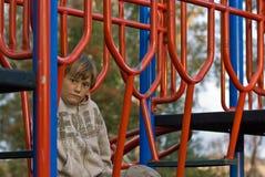 παιδική χαρά αγοριών λυπημέ& Στοκ Φωτογραφίες