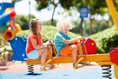 παιδική χαρά κατσικιών Τα παιδιά παίζουν στο θερινό πάρκο Στοκ εικόνα με δικαίωμα ελεύθερης χρήσης