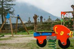 Παιδική χαρά κοντά στο νεκροταφείο μια βροχερή ημέρα νεφελώδης και με την ομίχλη στοκ εικόνα