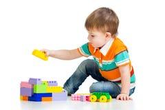 Παιχνίδια αγοριών κατσικιών με την κατασκευή που τίθεται πέρα από το λευκό Στοκ Εικόνα