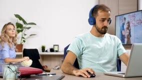Παιχνίδια ατόμων θορυβοδώς στον υπολογιστή ενώ η φίλη του προσπαθεί να προσέξει μια επίδειξη στη TV φιλμ μικρού μήκους