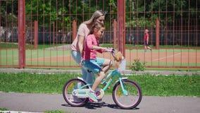 Παιχνίδια γυναικών με την κόρη της, που διδάσκει την για να οδηγήσει ένα ποδήλατο απόθεμα βίντεο