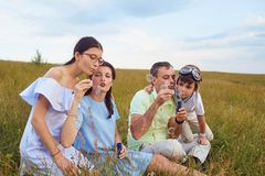 Παιχνίδια ευτυχή οικογενειών με τις θολωμένες φυσαλίδες στη φύση Στοκ φωτογραφία με δικαίωμα ελεύθερης χρήσης