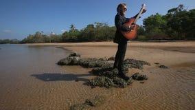 Παιχνίδια κιθαριστών masterly στο βράχο στην παραλία για το ξανθό κορίτσι απόθεμα βίντεο
