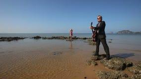 Παιχνίδια κιθαριστών masterly στο βράχο στην παραλία για το ξανθό κορίτσι φιλμ μικρού μήκους