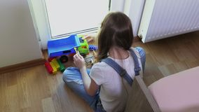 Παιχνίδια κοριτσιών με το αυτοκίνητο παιχνιδιών και τα τούβλα παιχνιδιών απόθεμα βίντεο