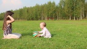 Παιχνίδια κοριτσιών με το μωρό και τη σφαίρα στον πράσινο τομέα απόθεμα βίντεο