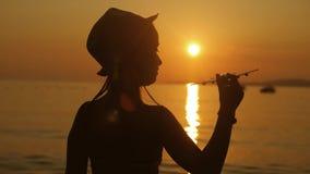 Παιχνίδια κοριτσιών σκιαγραφιών με ένα αεροπλάνο παιχνιδιών στην τροπική παραλία στο ηλιοβασίλεμα Χέρι με μικρό στενό επάνω αεροπ απόθεμα βίντεο