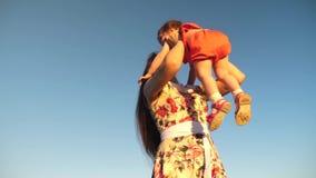 Παιχνίδια μητέρων με ένα μικρό παιδί ενάντια σε έναν μπλε ουρανό Το Mom ρίχνει την κόρη της μέχρι τον ουρανό ευτυχές οικογενειακό απόθεμα βίντεο