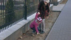 Παιχνίδια μητέρων με την κόρη της, άλματα κοριτσιών από το φράκτη Η έννοια της οικογένειας κίνηση αργή φιλμ μικρού μήκους