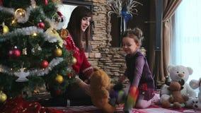 Παιχνίδια μητέρων με την κόρη της κοντά στο χριστουγεννιάτικο δέντρο φιλμ μικρού μήκους