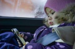 Παιχνίδια μικρά κοριτσιών στο τηλέφωνο καθμένος σε ένα αυτοκίνητο σε ένα κάθισμα παιδιών στοκ φωτογραφία
