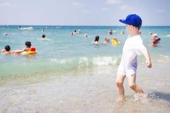 Παιχνίδια μικρών παιδιών στην παραλία θάλασσας Οι άνθρωποι κολυμπούν και χαλαρώνοντας στο θερμό νερό της θάλασσας Ηλιόλουστη θερι Στοκ Φωτογραφία