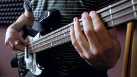 Παιχνίδια μουσικών στη βαθιά κιθάρα στο στούντιο απόθεμα βίντεο