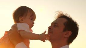 Παιχνίδια μπαμπάδων με την αγαπημένη κόρη του, ένα παιδί στα όπλα του πατέρα του ο μπαμπάς φιλά ένα μικρό παιδί στο πάρκο στο ηλι απόθεμα βίντεο