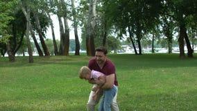 Παιχνίδια μπαμπάδων με το αγόρι στο πάρκο, που απολαμβάνει το θερινό Σαββατοκύριακο με το γιο, ενιαίος γονέας απόθεμα βίντεο