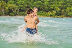 Παιχνίδια μπαμπάδων με το γιο του στη θάλασσα στοκ φωτογραφίες με δικαίωμα ελεύθερης χρήσης