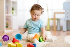 Παιχνίδια παιχνιδιού μικρών παιδιών μωρών στο σπίτι ή βρεφικός σταθμός Στοκ Εικόνα