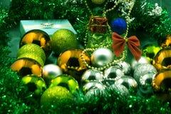 Παιχνίδια Χριστουγέννων που βρίσκονται στο πάτωμα κρεβατοκάμαρων με τον κόκκινο και πράσινο τάπητα η εορταστική εποχή Χριστουγένν Στοκ Φωτογραφίες