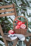 Παιχνίδια Χριστούγεννο-δέντρων σε ένα καλάθι και μάλλινα γάντια σε μια καρέκλα Στοκ Φωτογραφίες