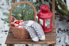 Παιχνίδια Χριστούγεννο-δέντρων σε ένα καλάθι και μάλλινα γάντια σε μια καρέκλα Στοκ Εικόνα