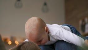 Παιχνίδια Mom με το μωρό στην άσπρη κορυφή δεξαμενών που βρίσκονται στο κρεβάτι, μωρό που πετά και που γελά Χρονικό σφάλμα να παί απόθεμα βίντεο