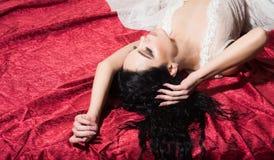 Παιχνίδι αγάπης Έννοια παιχνιδιών αγάπης παιχνίδι αγάπης της προκλητικής γυναίκας στο κόκκινο κρεβάτι παιχνίδι αγάπης και αποπλάν Στοκ Εικόνες