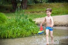 Παιχνίδι αγοράκι με το παιχνίδι σκαφών εν πλω Παιδί OS στις διακοπές το καλοκαίρι στην παραλία στις διακοπές Στοκ εικόνα με δικαίωμα ελεύθερης χρήσης