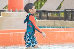 Παιχνίδι αγοριών δίπλα σε μια φωτογραφική διαφάνεια νερού στο πάρκο νερού aqua στοκ εικόνα