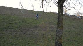 Παιχνίδι αγοριών με ένα αεροπλάνο παιχνιδιών στο πάρκο μια ηλιόλουστη ημέρα απόθεμα βίντεο
