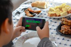 Παιχνίδι αγοριών με το τηλέφωνό του κατά τη διάρκεια του μεσημεριανού γεύματος Στοκ Φωτογραφία