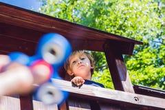 Παιχνίδι αγοριών με fidget τον κλώστη Περιστρεφόμενος κλώστης παιδιών στην παιδική χαρά ανασκόπηση που θολώνεται Στοκ Εικόνες