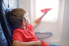 Παιχνίδι αγοριών παιδάκι με το κόκκινο αεροπλάνο εγγράφου κατά τη διάρκεια της πτήσης στο αεροπλάνο Στοκ Φωτογραφίες