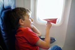 Παιχνίδι αγοριών παιδάκι με το κόκκινο αεροπλάνο εγγράφου κατά τη διάρκεια της πτήσης στο αεροπλάνο Στοκ Εικόνες