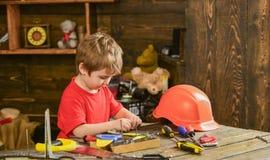 Παιχνίδι αγοριών παιδιών όπως handyman Έννοια παιδικής ηλικίας Χαριτωμένο και λατρευτό παιχνίδι παιδιών με τα εργαλεία ως οικοδόμ Στοκ Φωτογραφίες