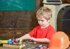 Παιχνίδι αγοριών παιδιών όπως handyman Χαριτωμένο και λατρευτό παιχνίδι παιδιών με τα εργαλεία ως οικοδόμο ή επιδιορθωτή, επισκευ Στοκ Εικόνα