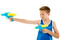 Παιχνίδι αγοριών προ-εφήβων με τα πυροβόλα όπλα νερού στοκ φωτογραφία με δικαίωμα ελεύθερης χρήσης