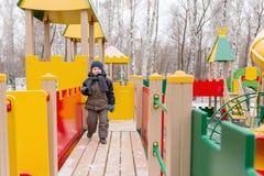 Παιχνίδι αγοριών σε μια παιδική χαρά παιδιών ` s Στοκ Εικόνες